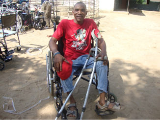 Mohamed Tarawalley, head of OTC in Kenema in receipt of a wheel chair and a set of crutches.